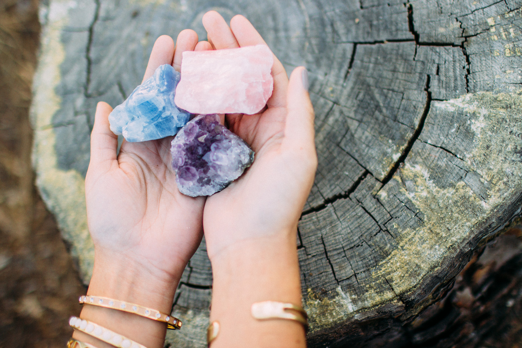 Crystals in hands over tree stump